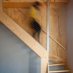 Idée de décoration pour un escalier sans contremarche urbain en L de taille moyenne avec des marches en bois.