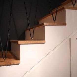 Diseño de escalera curva, escandinava, de tamaño medio, con escalones de madera, contrahuellas con baldosas y/o azulejos y barandilla de cable