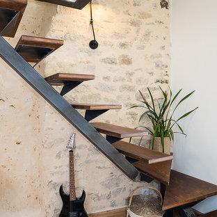 Idee per una scala curva design di medie dimensioni con pedata in legno e nessuna alzata