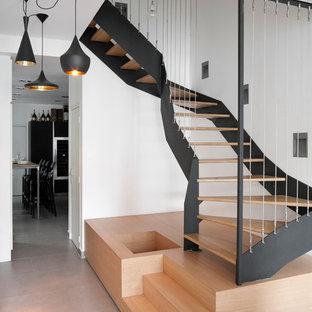 Esempio di una grande scala curva minimal con pedata in legno e nessuna alzata