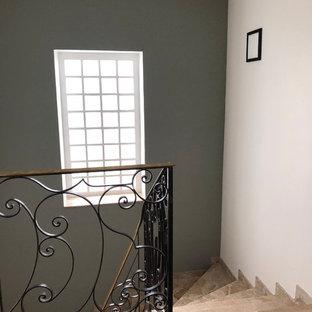 パリの広い大理石のコンテンポラリースタイルのおしゃれなサーキュラー階段 (大理石の蹴込み板、金属の手すり) の写真
