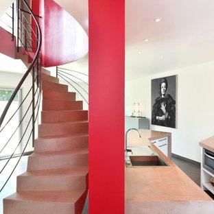 Réalisation d'un grand escalier courbe design avec des marches en béton et des contremarches en béton.