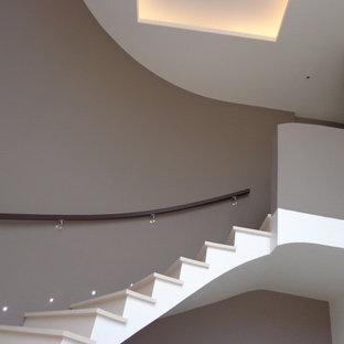 Immagine di una scala curva minimal di medie dimensioni con pedata in pietra calcarea e parapetto in legno