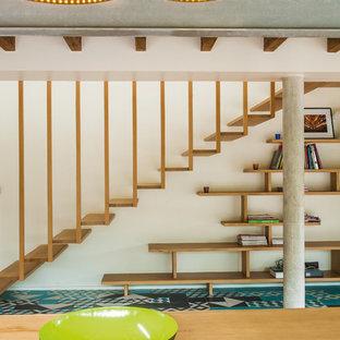 Réalisation d'un grand escalier sans contremarche flottant design avec des marches en bois.