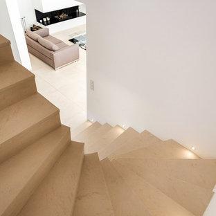 他の地域の大きいライムストーンのコンテンポラリースタイルのおしゃれな折り返し階段 (ライムストーンの蹴込み板) の写真