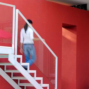 Ispirazione per una scala a rampa dritta design di medie dimensioni con parapetto in vetro