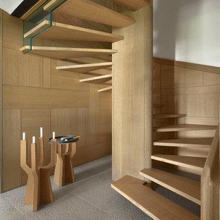 Ispirazione per una grande scala a chiocciola minimal con pedata in legno e nessuna alzata