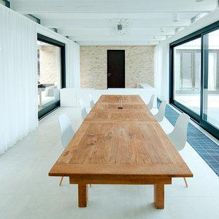 Foto di una grande sala da pranzo aperta verso il soggiorno minimal con pareti bianche, pavimento in gres porcellanato, camino classico e cornice del camino piastrellata