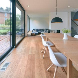 Idée de décoration pour une grande salle à manger ouverte sur le salon nordique avec un mur blanc, un sol en bois clair, une cheminée double-face et un manteau de cheminée en plâtre.