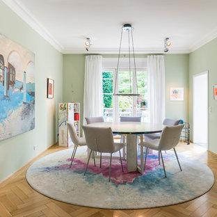 Geschlossenes Eklektisches Esszimmer mit grüner Wandfarbe, braunem Holzboden und beigem Boden in Köln