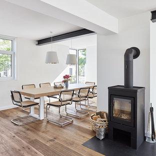 Immagine di una sala da pranzo aperta verso il soggiorno nordica di medie dimensioni con pareti bianche, parquet chiaro e stufa a legna