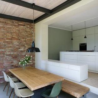 Ispirazione per una sala da pranzo aperta verso la cucina contemporanea di medie dimensioni con pareti rosse, pavimento in cemento e nessun camino