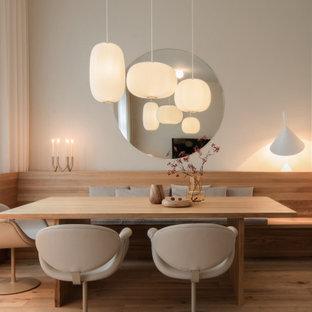 Imagen de comedor escandinavo, pequeño, sin chimenea, con paredes blancas, suelo de madera clara y suelo beige
