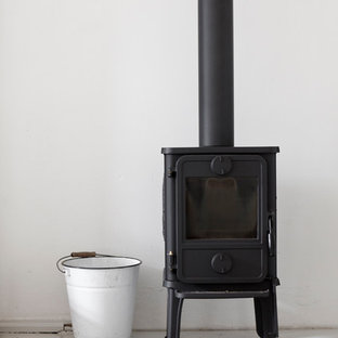 Mid-sized danish medium tone wood floor and gray floor enclosed dining room photo in Leipzig with white walls, a wood stove and a metal fireplace