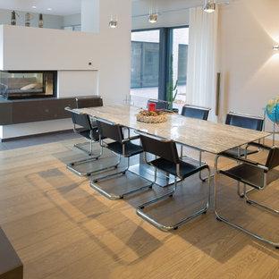 Immagine di un'ampia sala da pranzo aperta verso la cucina minimal con pareti marroni, pavimento in legno massello medio, stufa a legna, cornice del camino in mattoni e pavimento marrone