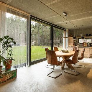 Große Retro Wohnküche ohne Kamin mit grauer Wandfarbe und Betonboden in Berlin