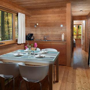 Kleine Urige Wohnküche mit brauner Wandfarbe, braunem Holzboden, braunem Boden und Holzwänden in Bremen