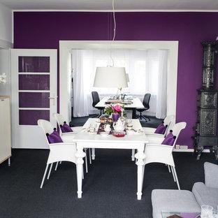 Esempio di una sala da pranzo aperta verso il soggiorno boho chic di medie dimensioni con pareti viola, moquette, pavimento nero, stufa a legna e cornice del camino in metallo