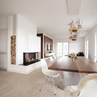 Esempio di una grande sala da pranzo aperta verso la cucina con pareti bianche, pavimento in ardesia, camino bifacciale, cornice del camino in intonaco e pavimento beige
