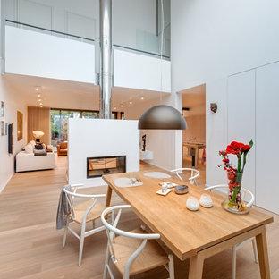 Offenes, Geräumiges Modernes Esszimmer mit weißer Wandfarbe, hellem Holzboden, Tunnelkamin, verputztem Kaminsims und braunem Boden in Köln