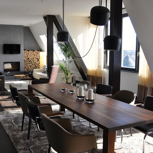 Imagen de comedor industrial, grande, con paredes blancas, suelo de madera oscura, estufa de leña, marco de chimenea de yeso y suelo marrón