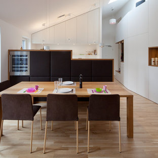 Mittelgroße Moderne Wohnküche ohne Kamin mit weißer Wandfarbe, hellem Holzboden und braunem Boden in München