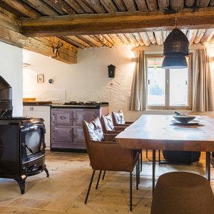 Diseño de comedor de cocina rústico, de tamaño medio, con paredes blancas, suelo de madera clara, estufa de leña y suelo beige
