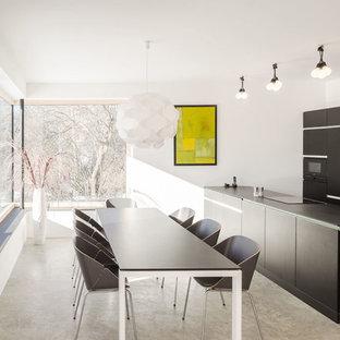Esempio di una sala da pranzo aperta verso la cucina minimalista di medie dimensioni con pareti bianche, pavimento in cemento, pavimento grigio e nessun camino