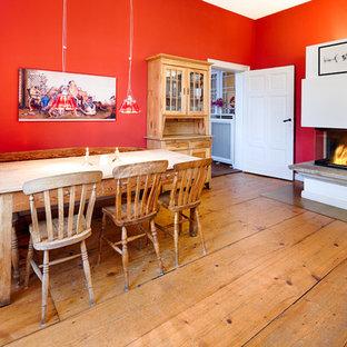 Ejemplo de comedor ecléctico, grande, abierto, con paredes rojas, suelo de madera oscura, marco de chimenea de yeso, suelo marrón y chimenea de esquina