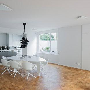 Offenes, Großes Modernes Esszimmer ohne Kamin mit weißer Wandfarbe, braunem Holzboden und braunem Boden in Berlin