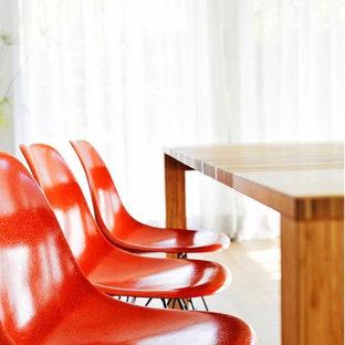 Exemple d'une très grand salle à manger ouverte sur le salon tendance avec un mur blanc, un sol en bois foncé, une cheminée standard, un manteau de cheminée en plâtre et un sol marron.
