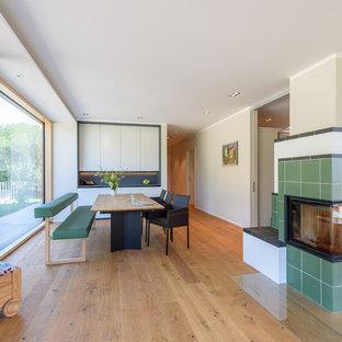 Offenes, Mittelgroßes Modernes Esszimmer mit beiger Wandfarbe, braunem Holzboden, Eckkamin, gefliestem Kaminsims und braunem Boden in Stuttgart
