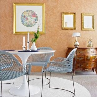 Idées déco pour une grande salle à manger ouverte sur le salon éclectique avec un mur orange, moquette, une cheminée d'angle, un manteau de cheminée en béton et un sol gris.