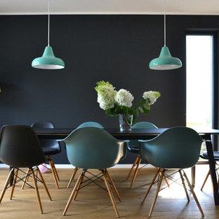 Ejemplo de comedor retro, de tamaño medio, abierto, con paredes negras y suelo de madera clara
