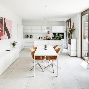 Moderne Wohnküche mit weißer Wandfarbe und grauem Boden in Sonstige