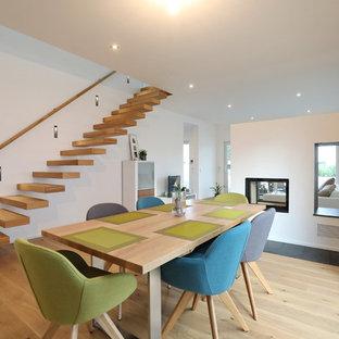 Cette photo montre une salle à manger scandinave de taille moyenne avec un mur blanc, une cheminée double-face, un sol en bois clair et un sol beige.