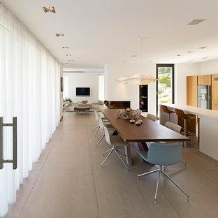 Inredning av ett modernt stort kök med matplats, med vita väggar, en dubbelsidig öppen spis, en spiselkrans i gips och linoleumgolv