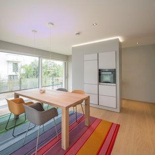 Moderne Wohnküche mit hellem Holzboden, grauer Wandfarbe und braunem Boden in Nürnberg