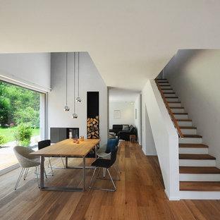 Mittelgroßes, Offenes Modernes Esszimmer mit grauer Wandfarbe, braunem Holzboden, Tunnelkamin, Kaminsims aus Metall und braunem Boden in Nürnberg