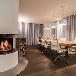 Geschlossenes, Großes Modernes Esszimmer mit weißer Wandfarbe, braunem Holzboden, Eckkamin, braunem Boden und verputzter Kaminumrandung in Stuttgart