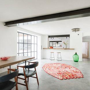 Imagen de comedor industrial, de tamaño medio, abierto, con paredes blancas, suelo de cemento, marco de chimenea de hormigón y suelo gris