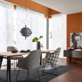 Geschlossenes, Mittelgroßes Modernes Esszimmer ohne Kamin mit oranger Wandfarbe, dunklem Holzboden und braunem Boden in Sonstige