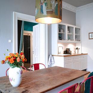Ejemplo de comedor de cocina ecléctico, de tamaño medio, con paredes grises y suelo de madera en tonos medios