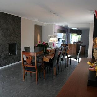 Idées déco pour une grand salle à manger ouverte sur le salon asiatique avec un mur blanc, une cheminée double-face et un sol noir.