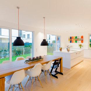 Große Moderne Wohnküche mit hellem Holzboden, beigem Boden und weißer Wandfarbe in Düsseldorf