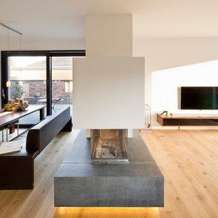 Immagine di una grande sala da pranzo aperta verso il soggiorno design con pareti bianche, parquet chiaro, camino bifacciale e cornice del camino in intonaco