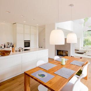 Idee per una grande sala da pranzo aperta verso il soggiorno scandinava con pareti bianche, parquet chiaro, cornice del camino in cemento e camino bifacciale