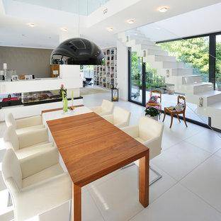 Immagine di un'ampia sala da pranzo aperta verso il soggiorno contemporanea con pareti bianche, pavimento in gres porcellanato, stufa a legna, cornice del camino in mattoni e pavimento bianco