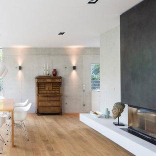 Idéer för stora eklektiska matplatser med öppen planlösning, med grå väggar, ljust trägolv, en bred öppen spis och en spiselkrans i metall