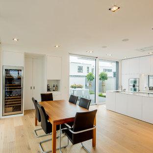 Große Moderne Wohnküche ohne Kamin mit braunem Holzboden, braunem Boden und weißer Wandfarbe in Düsseldorf